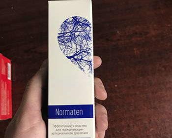 Упаковка Норматена белой стороной в руках